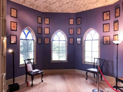 The window area of the Holbein Chamber in Strawberry Hill House.  There are three windows, purple walls and small pictures on the wall