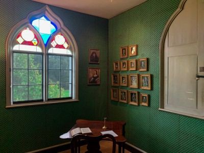 A small green room in Strawberry Hill House.  There is a small desk in the corner and a decorated window.