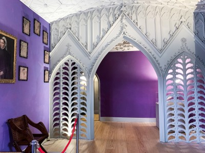 The Holbein Chamber in Strawberry Hill House.  There is a white arched divider in the middle of the room and purple walls