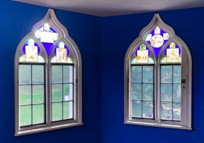 A room inside Strawberry Hill House - there are blue walls and two arches windows with coloured stained glass