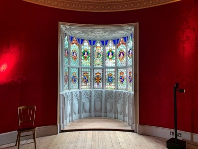 The round drawing room in Strawberry Hill House.  The walls are red and there is a bay window with colourful stained glass