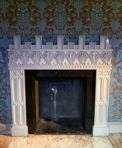 A fireplace in Strawberry Hill House - it is square and white with blue and gold patterned wallpaper on the wall behind
