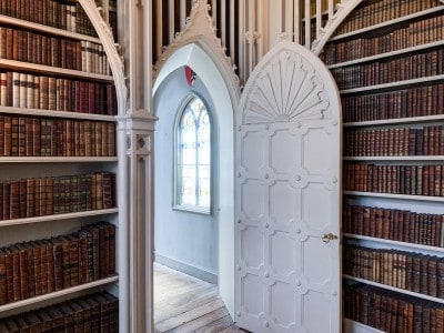 A white arched door leading into the library at Strawberry Hill House.  There are books on the shelve to the side