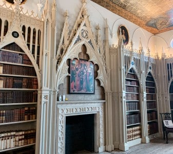 A view of part of the library that you can see in Strawberry Hill House on a day trip from London by train.  There are carved gothic shelves and a fireplace and books on the shelves
