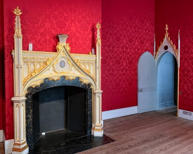 A room in Strawberry Hill House - there are red wall and a gold trimmed gothic fireplace