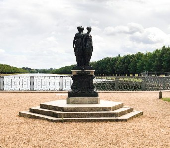 Part of the palace gardens with a statue and a view of the Long Water canal