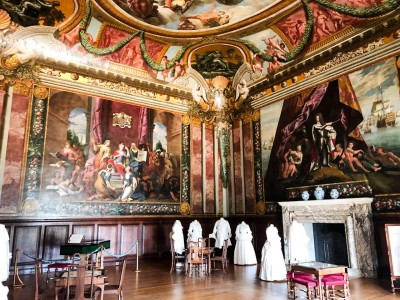 Inside the Queen's Drawing Room with it decorated walls and dresses on show
