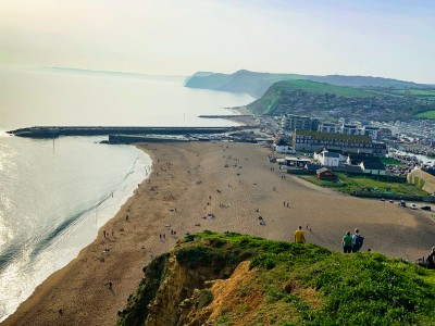 A view back down over the beach and town of West Bay from the top of the cliff