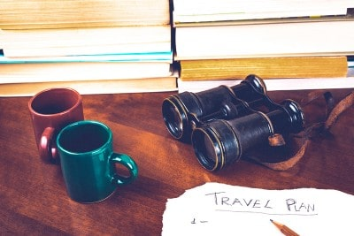An image of book, mugs and binoculars, along with the start of a written travel plan