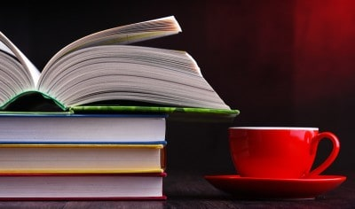 A pile of books on a coffee table with a red cup and saucer