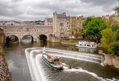 A boat on the River Avon near the weir and bridge - you can take a trip on a boat on your weekend in Bath
