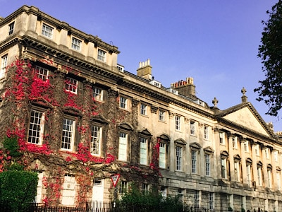 A Georgian building in Bath - part of it has colourful vines creeping up the front