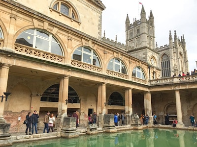 A view of the Great Bath in the Roman Baths Museum with bath Abbey in the background