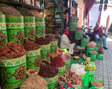 Some drums of spices that are outside a shop in the souks