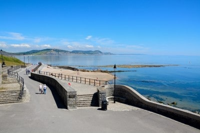The pedestrianised Gun Cliff Walk in Lyme regis and the view out the sea.  There are cliffs in the background