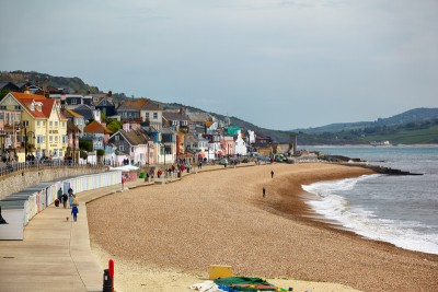 A view of the main beach in Lyme Regis with the promenade and houses in the background