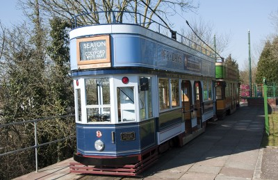 A blue open top tram that you can ride on on the SeatonTramway