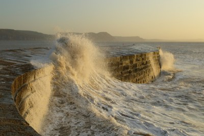 The Cobb Lyme Regis in stormy weather with waves whipping over it