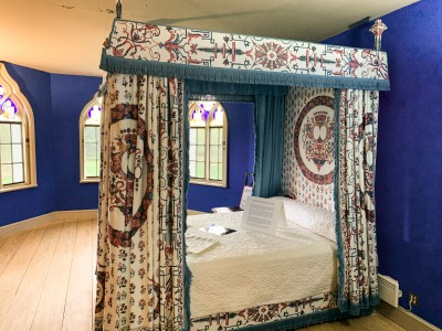 A blue room at Strawberry Hill House with a four poster bed in it and stained glass windows