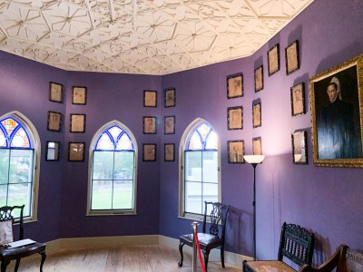 A purple painted room in Strawberry Hill House with an ornate ceiling and stained glass arched windows