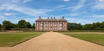 A view of Ham House with lawns and a path leading up to it