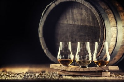 An image of some whisky glasses in front of a barrel