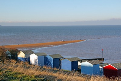 A view of 'The Street' - a spit of shingle in the sea - in Whitstable with beach huts in front